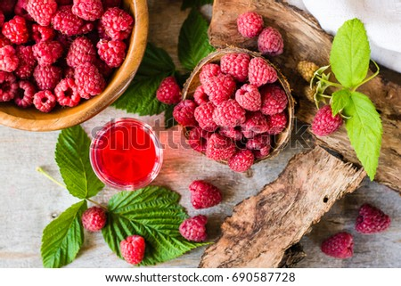 Boiling raspberry drink and berries in a bowl. Top view #690587728
