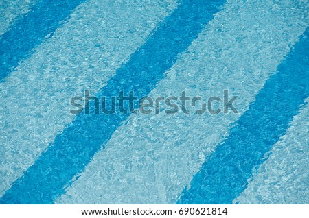 A semi-abstract image of the stripes painted on the bottom of an outdoor swimming pool, with water rippling over the top of them. Suitable for use as a Summer-themed background. #690621814
