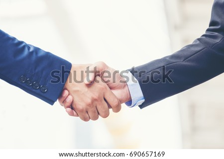 Business partnership meeting concept. Image businessmans handshake. Successful businessmen handshaking after good deal. Horizontal, blurred background Royalty-Free Stock Photo #690657169