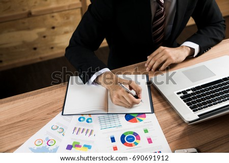 business person making a note on the desk.