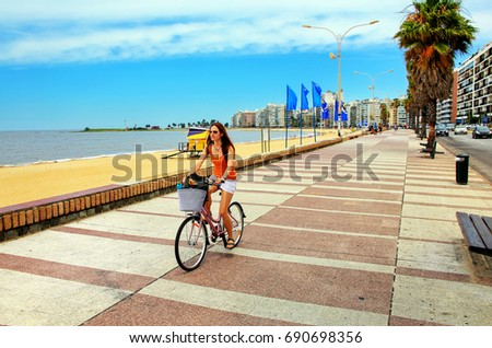 Woman biking on the boulevard along Pocitos beach in Montevideo, Uruguay. Montevideo is the capital and the largest city of Uruguay #690698356