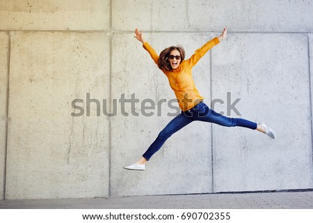 Joyful young lady jumping and raising arms in front of wall outside Royalty-Free Stock Photo #690702355