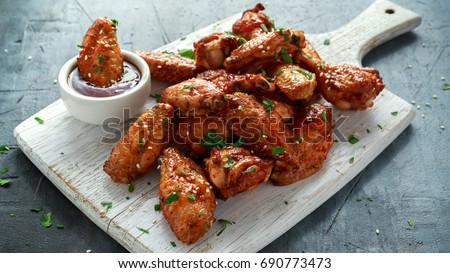 Baked chicken wings with sesame seeds and sweet chili sauce on white wooden board. Royalty-Free Stock Photo #690773473