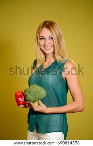 Portrait of young beautiful woman  holding a vegetable on yellow background  #690814576