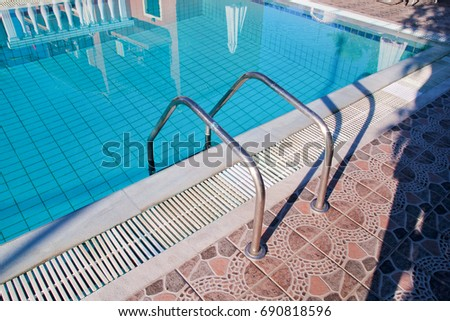 Handrail on the pool. Pool handrails view. Water swimming pool with stair with sunny reflections, closeup. Steel handrail, swimming, summer, travel. The entry to the pool with handrail. #690818596