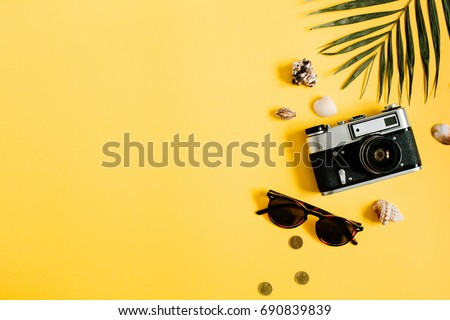 Flat lay traveler accessories on yellow background with palm leaf, camera and sunglasses. Top view travel or vacation concept. Summer background. #690839839