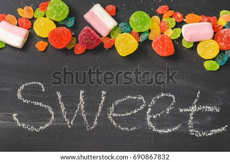 Bright colored candy, sweets on a dark background, top view #690867832