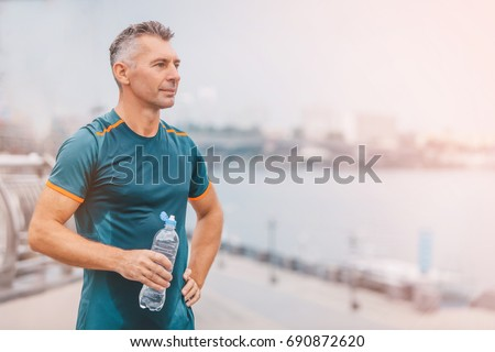 Portrait of healthy athletic middle aged man with fit body holding bottle of refreshing water, resting after workout or running. middle aged male with a drink after outdoor training.  Royalty-Free Stock Photo #690872620