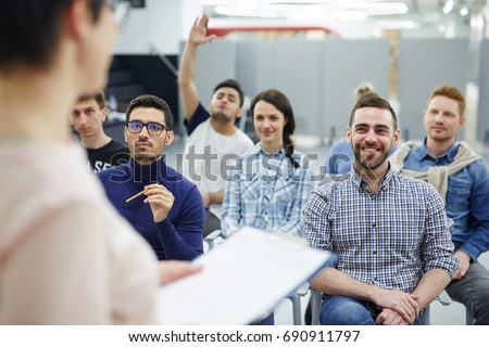 Groupmates listening to lecturer or speaker at conference Royalty-Free Stock Photo #690911797