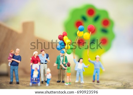 Miniature people, family and children with colorful balloons  standing in front of house. International Day of Families #690923596
