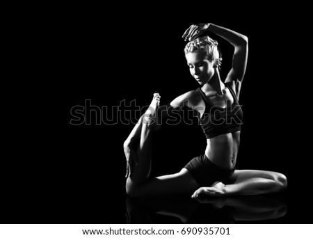 Black and white picture of a woman practicing pigeon yoga pose