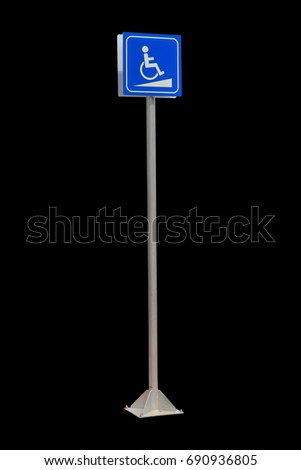 Disabled parking space and wheelchair way sign and symbols on a pole warning motorists isolated on black background