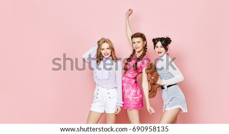 Fashion photo of three young girl posing over pink background in studio #690958135