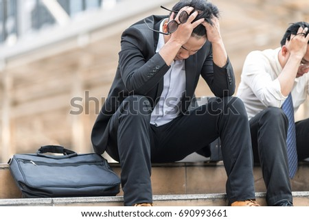 Serious and depressed  tired asian businessman tired from work sitting at stairs, unemployment, fired from job, disappointed, loss and feeling down concept .On view metropolis city background. #690993661