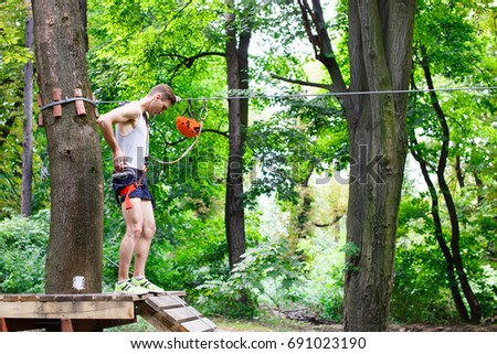 Man prepares to climb on the ropes in the park #691023190