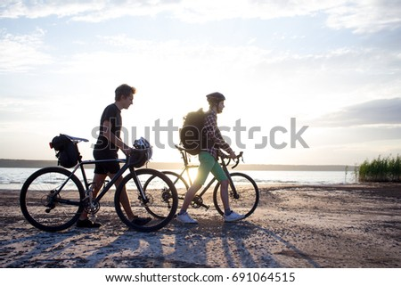 Two tourists with bicycle walking in the desert during the sunset in lake  #691064515