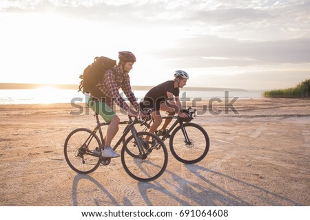 Two young male on a touring bicycle with backpacks and helmets in the desert on a bicycle trip #691064608