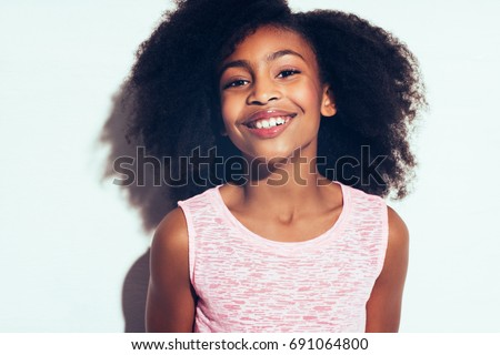 Cute young African girl with long curly hair smiling confidently while standing by herself against a gray background #691064800