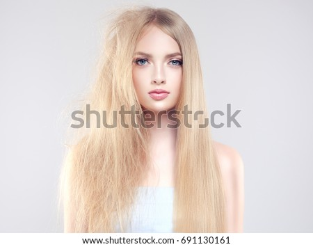 Hair care . Straightening ,smoothing and treatment of the hair .  Girl with straight and smooth hair on one side of the head . The second side of the head tangled and unbrushed hair . Royalty-Free Stock Photo #691130161