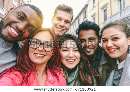 Happy friends from diverse cultures and races taking selfie with back lighting - Youth and friendship concept with young people having fun together - Main focus on left two guys - Retro filter #691180921