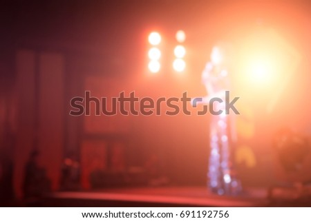 Disfocus of female speakers on the stage under the color full of downlight with Rear view of Audience in the conference hall or seminar meeting, business and education concept #691192756