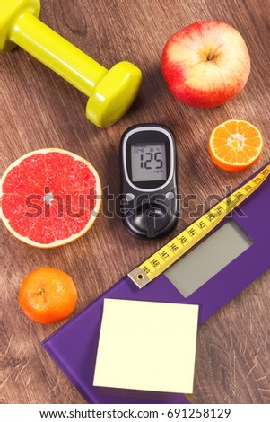 Electronic bathroom scale and glucose meter with result of measurement sugar level, concept of healthy lifestyles, diabetes and slimming #691258129