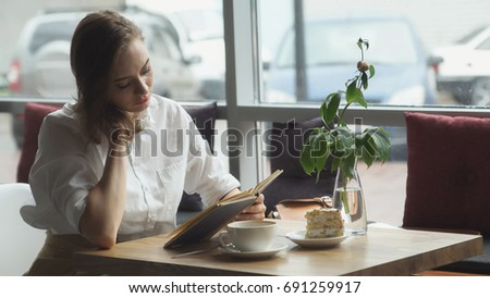 Girl reading book and relaxing in the cafe. girl in business clothes resting during the lunch break. #691259917