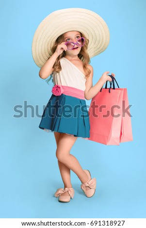 The cute little caucasian brunette girl in dress holding shopping bags #691318927