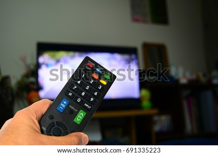 remote control in hand and television monitor #691335223