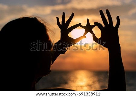 Girl on the seashore is holding a starfish. Silhouetted photo in the sun lights #691358911