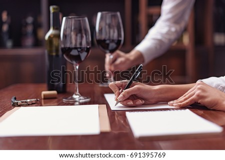 Two sommeliers, male and female tasting red wine and making notes at degustation card #691395769