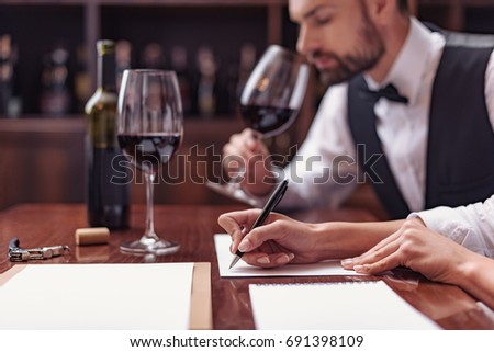 Two sommeliers, male and female tasting red wine and making notes at degustation card #691398109