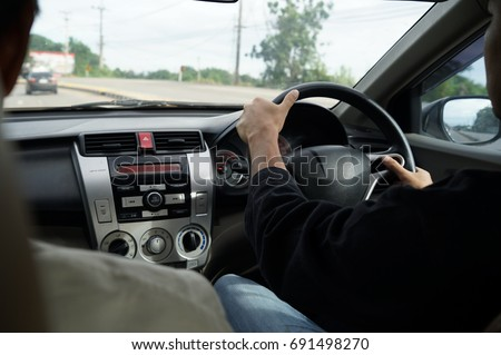 Right hand drive car. Man hands holding steering wheel. #691498270