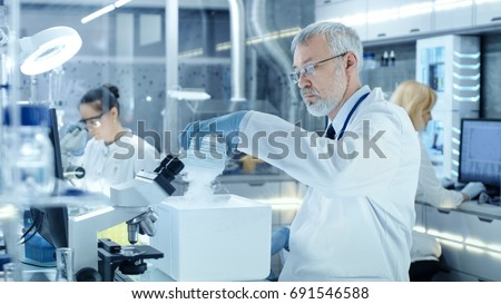 Senior Medical Research Scientist Takes Out Petri Dish with Samples from Opened Refrigerator Box. He Works in a Busy Modern Laboratory Center. #691546588
