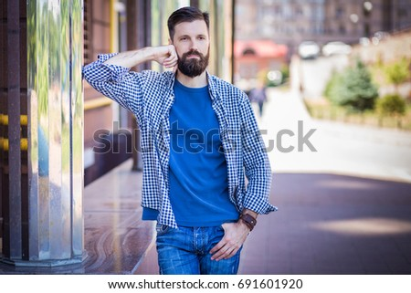 Stylish hipster man posing against city background #691601920