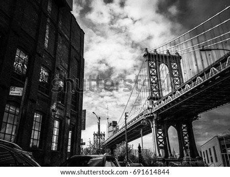 Manhattan bridge and buildings with cloudy sky in black and white #691614844