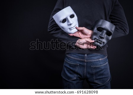 Mystery man holding black and white mask. Anonymous social masking concept. Royalty-Free Stock Photo #691628098
