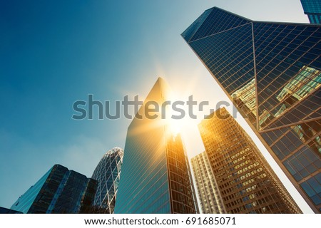 Skyscraper glass facades on a bright sunny day with sunbeams in the blue sky. Modern buildings in Paris business district La Defense. Economy, finances, business activity concept. Bottom up view #691685071