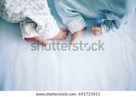 Small legs of two newborn twins in panties on a blue background. Happy Family concept. Beautiful conceptual image of Maternity