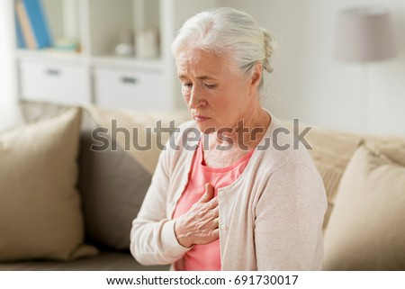 old age, health problem and people concept - senior woman suffering from heartache at home #691730017