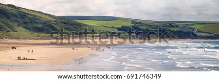 Panoramic view of the beach of Woolacombe. Waves on the sea and people on the shore. Royalty-Free Stock Photo #691746349