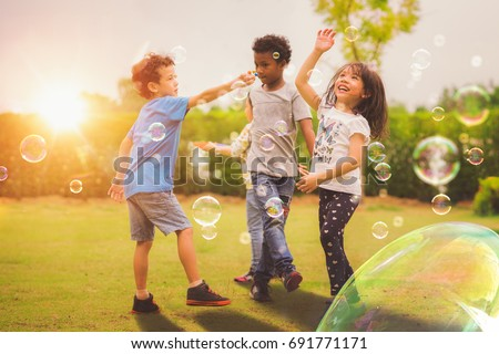 Kid and friends in international preschool play a bubble in playground with sunset background, kid, child, school, play and summer background Royalty-Free Stock Photo #691771171