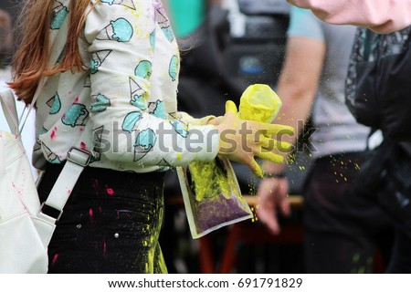 Girl pours dry yellow powdery paint on her friend at the festival of Holi festival in Gatchina, Russia #691791829