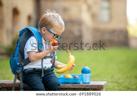 Cute schoolboy eating outdoors the school from plastick lunch boxe. Healthy school breakfast for child. Food for lunch, lunchboxes with sandwiches, fruits, vegetables, and water.  Royalty-Free Stock Photo #691889026