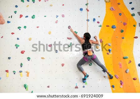 Woman climbing on the wall, view from the back #691924009