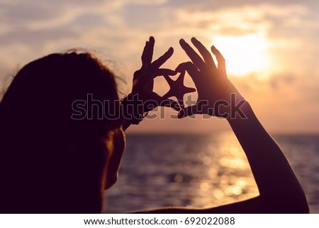 Girl on the seashore is holding a starfish. Silhouetted photo in the sun lights #692022088
