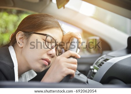 Tired Asian Business woman sleeping while driving a car. Illness, exhausted, disease, for overtime working concept. #692062054