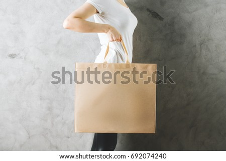 Side view and close up of woman holding empty shopping bag on concrete wall background. Logo concept. Mock up  #692074240