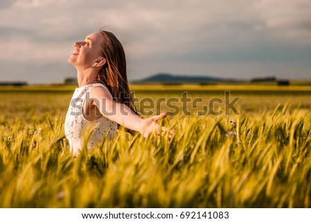 Beautiful woman in white dress on golden yellow wheat field in warm sunshine under dramatic sky, fresh vibrant colors, at Rhine Valley (Rhine Gorge) in Germany #692141083