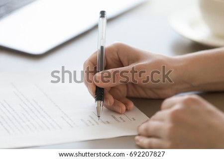 Businesswoman signing document concept, focus on female hand holding pen, putting signature on legal document, giving permission by authorization, subscribing contract, binding agreement, close up #692207827